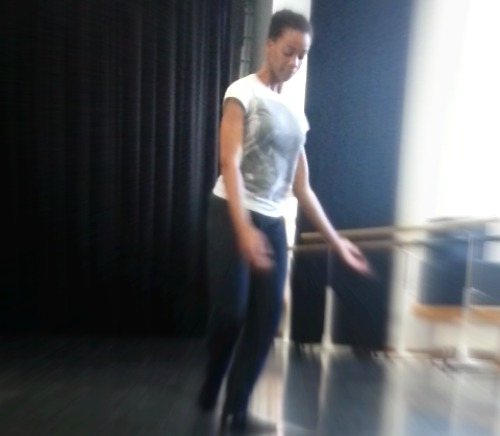 A dancer improvising a dance in a dance studio.