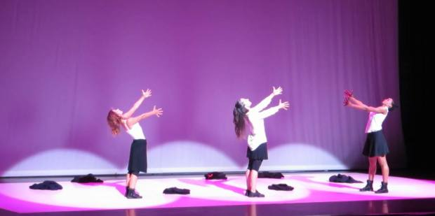 Three dancers performing on a stage with arms outstreched.